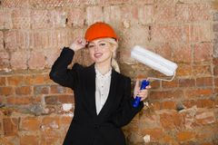 Portrait of architect student or painter with paint roller and protect helmet wearing. Brick red background. Portrait of architect student or painter with paint Stock Image