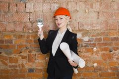 Portrait of architect student or painter with glass of wine and protect helmet wearing. Brick red background. Portrait of architect student woman with Stock Photography