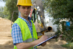 Portrait of architect using clipboard at construction site Royalty Free Stock Images