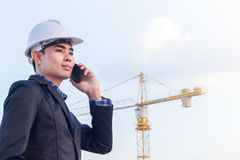Portrait of architect wear white helmet safty talking with smartphone on construction site with crane background. Portrait of architect wear white helmet safety stock photos
