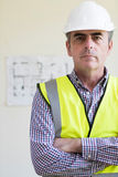 Portrait Of Architect Wearing Hard Hat With Plans In Background