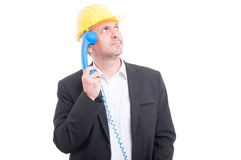 Portrait of architect wearing hardhat making thinking gesture Royalty Free Stock Photo