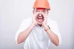 Portrait of architect wearing  hardhat screaming out loud. On grey background Stock Image