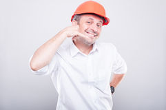 Portrait of architect wearing  hardhat showing calling gesture Stock Photography