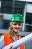 Portrait of architect woman in hardhat holding blueprints Stock Image