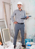 Portrait of architect working at the notebook in helmet with doc Royalty Free Stock Image
