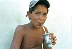 Portrait of Argentinian boy drinking herbal mate. Argentina, province of Buenos Aires, city Lanus: in the slum La Torre there is a child drinking, like a real royalty free stock image