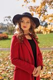 Portrait of an aristocratic girl walking in an autumn park in a red coat and a black hat. Portrait of an aristocratic young girl walking in an autumn park in a Stock Photo