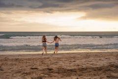 Portrait arrière de deux heureux et d'amies attirantes de jeunes femmes tenant des mains sur la plage fonctionnant à la mer sous  photo stock