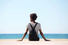 Portrait arrière de jeune femme se reposant par la plage le jour d'été Photos libres de droits