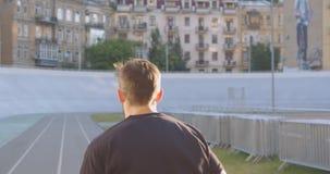 Portrait arrière de vue de plan rapproché du coureur masculin sportif caucasien adulte pulsant sur le stade dans la ville urbaine banque de vidéos