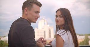 Portrait arrière de vue de plan rapproché de jeunes couples caucasiens mignons regardant la belle vue et se tournant vers la camé banque de vidéos
