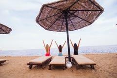 Portrait arrière de vue de trois amis sexy de femmes s'asseyant et se reposant dans les chaises longues avec le parapluie sur la  Photo libre de droits