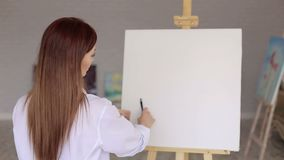 Portrait of an artist girl in front of a white canvas on an easel. Portrait of an artist girl in front of a white canvas on an easel, she decides where to start stock video