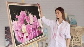 Portrait of an artist girl near a picture with flowers of peonies. stock video