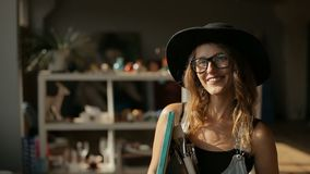 Portrait of Artist. Portrait of smiling artist, tall and slim woman holding big picture and different paintbrushes, wearing elegant black hat and denim jumpsuit stock video