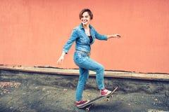 Portrait Artsy d'une fille mignonne de brune sur une planche à roulettes, riant et profitant d'un agréable moment Concept de la v Image stock