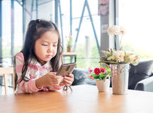 Portrait of Asia pretty little girl play mobile phone Royalty Free Stock Photos