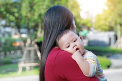 Portrait of Asian baby boy lying in hug of mother.  royalty free stock photography