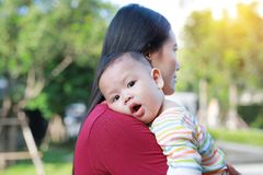 Portrait of Asian baby boy lying in hug of mother with looking camera.  royalty free stock photo