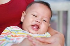 Portrait of Asian baby boy lying in hug of mother with looking camera.  royalty free stock photography