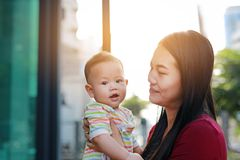 Portrait of Asian baby boy lying in hug of mother with looking camera.  stock photo
