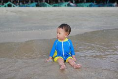 Portrait of Asian baby boy in swimming suit sitting on the sand beach royalty free stock photos