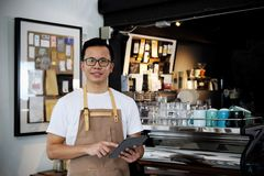 Portrait of asian barista holding digital tablet at counter in c. Portrait of smiling asian barista holding digital tablet at counter in coffee shop. Cafe Stock Photos