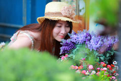 Portrait asian beautiful girl wear floral maxi dress. Brown hat in colorful floral garden Royalty Free Stock Image