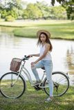 Brunette girl with bicycle in park. Portrait of Asian Beautiful woman hold bicycle near the pond in park. People Healthy and sport lifestyle concept. Brunette stock photography