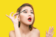 Portrait of Asian Beautiful woman with makeup brush near her face against yellow background stock photo