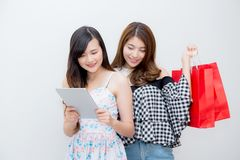 Portrait of asian beautiful young two people woman holding shopping bag and tablet computer. Portrait of asian beautiful young two people women holding shopping royalty free stock image