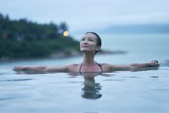 Portrait of Asian beauty smiling and relaxing in pool at dawn royalty free stock photo