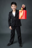 Portrait of asian boy in black suit holding gift bag Stock Photography