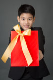 Portrait of asian boy in black suit holding gift bag Royalty Free Stock Photos
