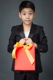 Portrait of asian boy in black suit holding gift bag Stock Photo