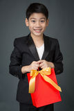 Portrait of asian boy in black suit holding gift bag Royalty Free Stock Images