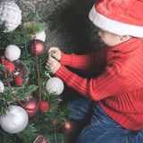 Portrait of asian boy decorating Christmas tree, dressed Santa hat Royalty Free Stock Photos