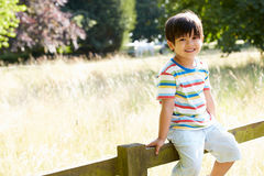 Portrait Of Asian Boy Sitting On Fence In Countryside Stock Image