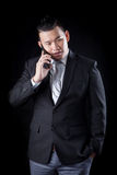 Portrait of asian business man talking mobile phone against blac Stock Images