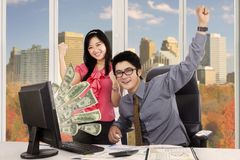 Happy business people with money on computer Royalty Free Stock Photos