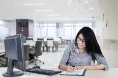 Asian business woman writing on the clipboard. Portrait of an Asian business woman writing on the clipboard by using a pen while sitting in the office Stock Photography