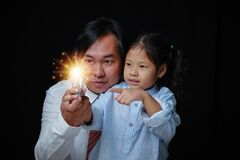 Portrait Asian businessman and kid girl holding light bul.