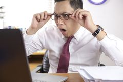 Asian Businessman Working on Laptop Shocked Stunned gesture. Portrait of Asian businessman looking at his laptop with shocked stunned worried facial expression royalty free stock photo