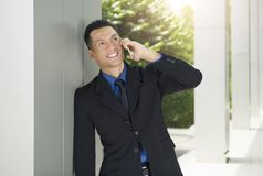 Portrait of asian businessman relax while talking on the phone. Outside office room Stock Image