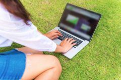 Portrait of asian businesswoman using laptop on garden grass. Technology concept Royalty Free Stock Image