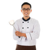 Portrait of Asian chef. Holding spatula, smiling and standing isolated on white background Stock Image