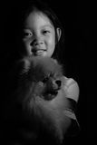 Portrait Asian Child Holding Dog in Black and White. Black and white portrait of Asian child holding dog Stock Photo