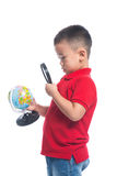 Portrait asian child holding earth globe map in his hand, lookin. G through magnifying loupe Royalty Free Stock Photography