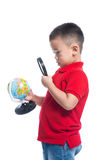 Portrait asian child holding earth globe map in his hand, lookin. G through magnifying loupe Stock Images